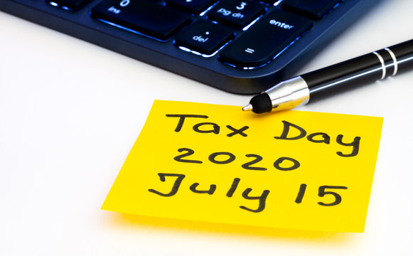 Tax day postponed by american government to July 15th 2020. Tax reminder concept with yellow sticky note, illuminated computer keyboard and pen on white background. Due taxes in United States