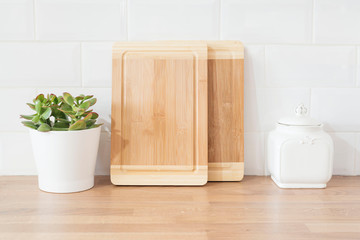 Bright And Clean Modern Minimalist Kitchen, Close Up. Cutting Boards, Green Succulent Pot On A Wooden Worktop
