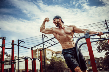 Photo sur Aluminium Singe Bearded bodybuilder man exercising on monkey bars for the upper-body in a modern calisthenics park outdoors on a sunny day. Show biceps and scream for motivation.
