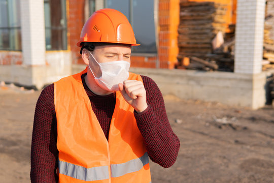 Male construction worker in overalls and medical mask coughing on background of house under construction. Concept of threat of infection.
