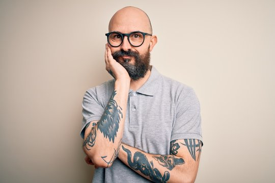 Handsome bald man with beard and tattoo wearing casual polo and glasses thinking looking tired and bored with depression problems with crossed arms.
