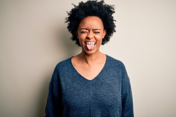 Young beautiful African American afro woman with curly hair wearing casual sweater sticking tongue out happy with funny expression. Emotion concept. Wall mural