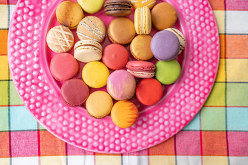 Wall Murals Macarons Many french macarons selection of colorful pastries on pink dessert plate top view. Retro vintage home kitchen background. Assortment of fancy pastry macaroons tasting.