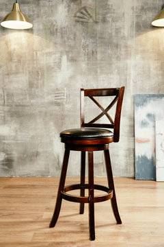 Wooden bar stool and stucco wall background, front view