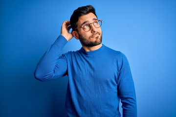 Young handsome man with beard wearing casual sweater and glasses over blue background confuse and wondering about question. Uncertain with doubt, thinking with hand on head. Pensive concept.