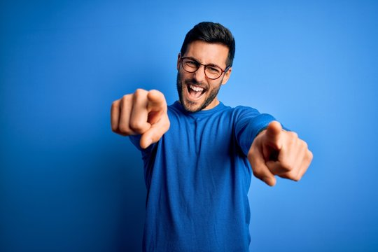 Young handsome man with beard wearing casual sweater and glasses over blue background pointing to you and the camera with fingers, smiling positive and cheerful