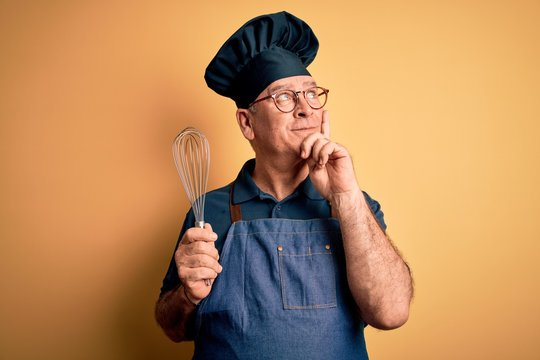 Middle age hoary cooker man wearing apron and hat holding whisk over yellow background serious face thinking about question, very confused idea