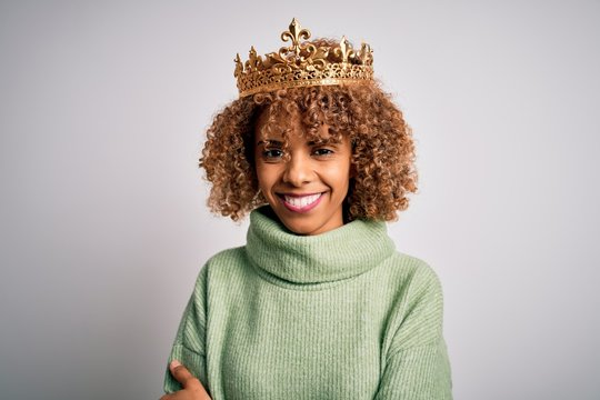 Young african american woman wearing golden crown of queen over isolated white background happy face smiling with crossed arms looking at the camera. Positive person.