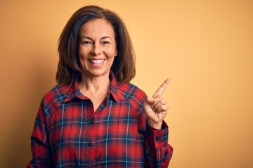 Wall Mural - Middle age beautiful woman wearing casual shirt standing over isolated yellow background with a big smile on face, pointing with hand finger to the side looking at the camera.