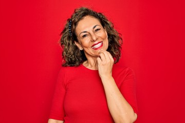 Wall Mural - Middle age senior brunette woman wearing casual t-shirt standing over red background looking confident at the camera with smile with crossed arms and hand raised on chin. Thinking positive.