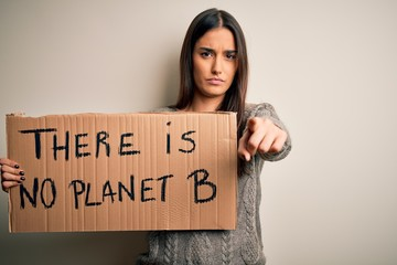 Young beautiful brunette activist woman protesting for save the planet holding banner pointing with finger to the camera and to you, hand sign, positive and confident gesture from the front