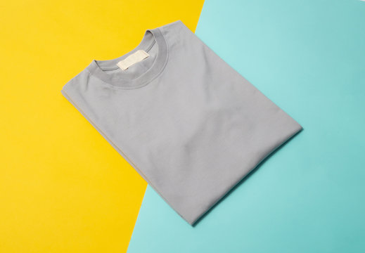 Grey folded t-shirt isolated on yellow and blue background.