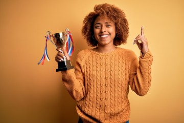 Young African American afro woman with curly hair holding winner champion trophy surprised with an idea or question pointing finger with happy face, number one
