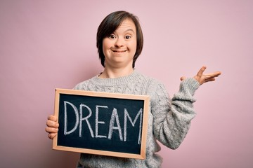 Young down syndrome woman holding blackboard with dream word as message of happiness very happy and excited, winner expression celebrating victory screaming with big smile and raised hands