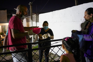 People receive a free dinner made by the Salazar family who cooked for their neighbours, many of whom have lost their jobs as a consequence of the coronavirus disease (COVID-19), in Montevideo