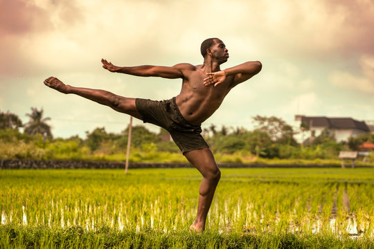 ballet dancer and choreographer workout - young athletic and fit black African American man dancing free outdoors on tropical rice field background in fitness  body expression concept