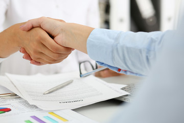 Partnership agreement closeup with woman in suit shake hand as hello in background. Friend welcome mediation offer greet gesture participate approval motivation strike arm bargain concept