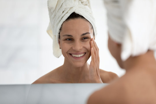 Woman wrapped white bath towel on head reflecting in bathroom mirror, awakened female with toothy smile touch face feels satisfied by healthy ideal perfect skin after cream or mask home spa procedure
