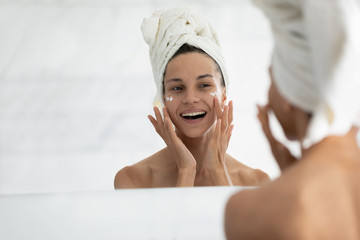 Printed kitchen splashbacks Spa View over shoulder, beautiful woman wrapped in towel looking in mirror while applied face cream provide deeper repair, protecting facial skin. Skincare, beauty effective anti wrinkle treatment concept