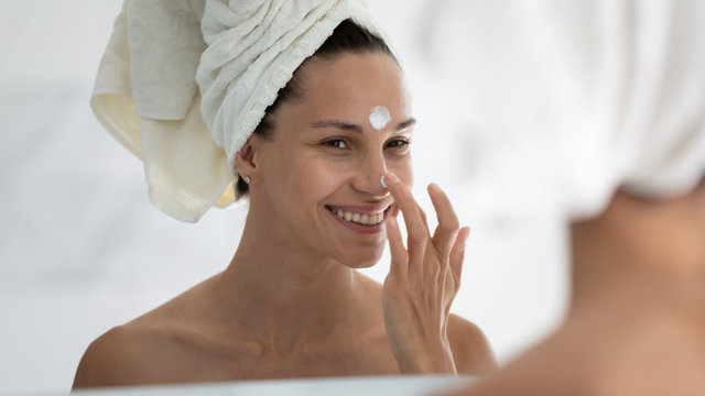Woman reflected in mirror after morning shower with towel on head applies day facial cream close up, prevent first wrinkles, caring about skin use moisturizer creme, beauty treatment, skincare concept