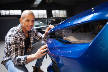 Selective focus on car lights, happy man cleaning automobile carefully at his garage