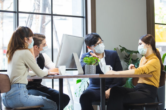Group of business people with wearing hygienic mask prophylactic manager talking in meeting work room planning.