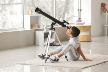 Little African-American boy with telescope at home