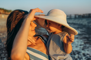 Side view image of happy smiling young mother and her little daughter has fun at the sea sunset. Beautiful female with baby playing outside together at the ocean beach on sunset. Motherhood love care.