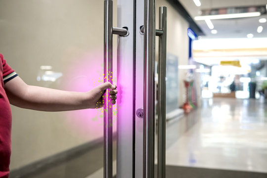 The boy is opening the door to the mall where a virus or bacteria is stuck on the door handle.
