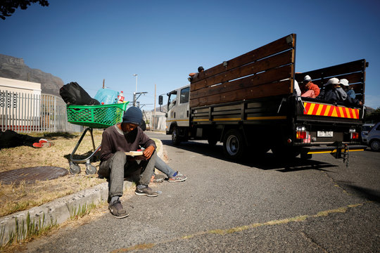 A homeless man reads a book while waiting for the completion of a shelter that city officials were setting up as part of a 21 day nationwide lockdown aimed at limiting the spread  of coronavirus disease (COVID-19) in Cape Town