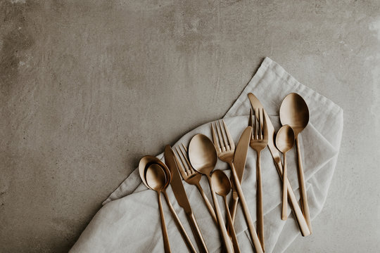 Golden cutlery composition on grey background