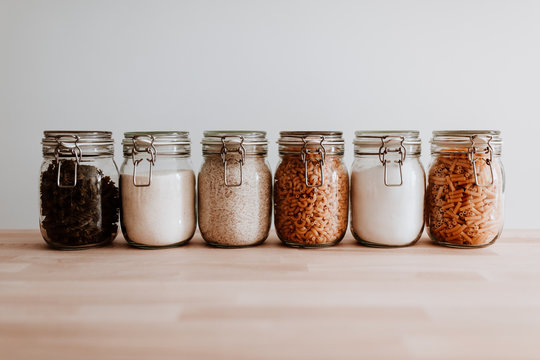 Six glass jars full with dried uncooked food ingredients