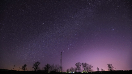 Fotorollo Aubergine lila Real Night Sky Stars Above Landscape With Telecommunications Cell Phone Tower Or With Antenna. Natural Starry Sky With Milky Way Galaxy Above Rural Countryside Landscape In Belarus