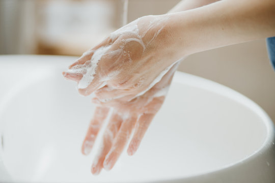 Closeup of a woman washing her hands in bathroom to prevent Covid-19 viral infection. Recommended washing with soap and running water during coronavirus pandemic.