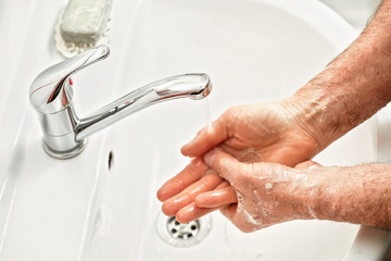 Senior elderly man his hands palms with soap under tap water faucet, detail photo. Can be used as...