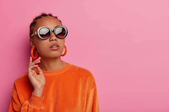 People, fashion, luxury concept. Stylish dark skinned woman wears fashionable orange jumper, earrings and sunglasses, raises head, has well cared skin, isolated on pink background, blank space