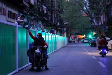 A delivery worker passes a parcel to a man over barriers separating residential buildings from a street in Wuhan