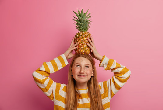 Funny kid carries pineapple on head, has freckled skin, plays with tropical fruit, has long ginger hair, dressed in striped jumper, poses against pink background in studio. Children, lifestyle concept