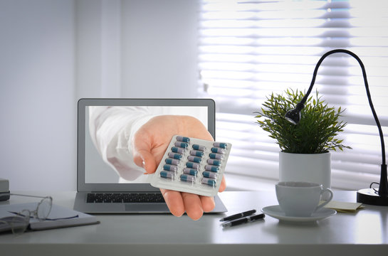 Ordering medications online. Pharmacist giving pills from laptop screen
