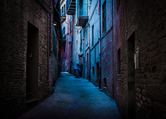 An atmospheric, narrow, back alley painted with blue and magenta light taken in Recanati, Macerata, Italy