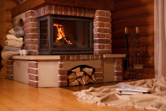 Fireplace with burning wood in room. Winter vacation