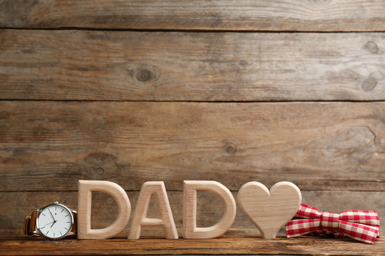 Composition with word DAD and heart on wooden background, space for text. Happy Father's day