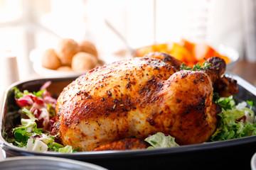 Foto op Plexiglas Kip Whole roasted chicken with fresh salad in black dish