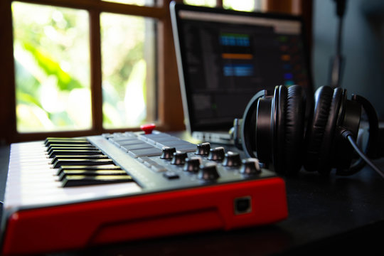 Midi keybard in a music producer home studio, desk with headphones and a notebook. Window with nature in the background.