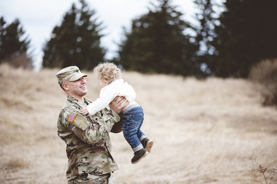 Shallow focus shot of a smiling American soldier carrying his baby