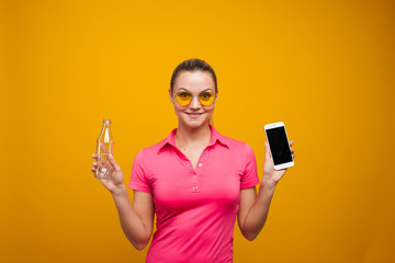 Healthy habits, an app to track the amount of water you drink. Young woman with a bottle of water and a smartphone
