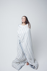Healthy sleep and drowsiness, beautiful young woman standing wrapped in a blanket