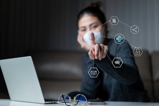 Asia woman wearing surgical mask on face protective for spreading of disease Covid-19 pandemic Coronavirus.  Young Adult Asian using laptop while sitting on sofa with virtual graphic icon diagram.