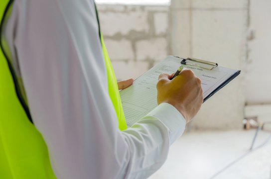 foreman builder, engineer or inspector in green safety vest reflective checking and inspecting with clipboard at construction site building interior, inspection, contractor and engineering concept