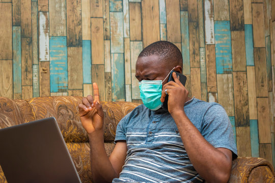 young black man working on his laptop, pressing a phone and preventing himself with a nose mask